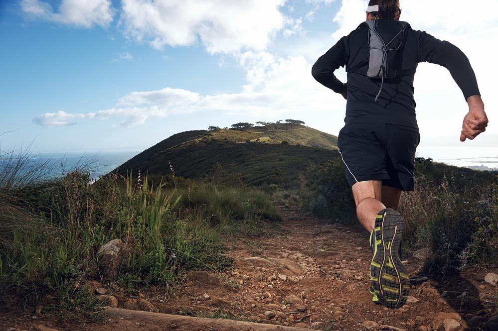 trail running man on mountain path exercising