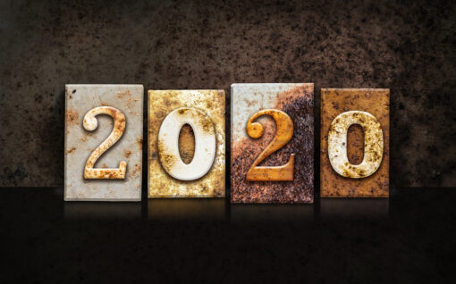 "The word ""2020"" written in rusty metal letterpress type on a dark textured grunge background."
